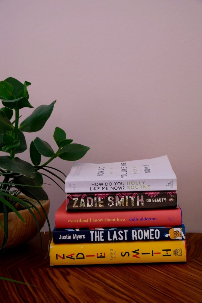 stack of books pink wall